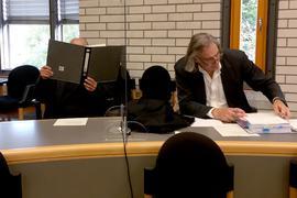 """30.09.2020, Baden-Württemberg, Baden-Baden: Ein Angeklagter in einem Prozess um eine Gruppenvergwaltigung hält sich vor Prozessbeginn im Gerichtsaal einen Aktenordner vor sein Gesicht. Rechts sitzt sein Anwalt Andreas Kniep. Vor mehr als 30 Jahren soll sich der Angeklagte als Leiter einer Pfadfindergruppe der Gruppenvergewaltigung schuldig gemacht haben. (zu dpa: """"Vergewaltigtes Mädchen - Mann nach mehr als 30 Jahren vor Gericht"""") Foto: Sönke Möhl/dpa - ACHTUNG: Unterlagen wurden aus rechtlichen Gründen teilweise gepixelt +++ dpa-Bildfunk +++"""