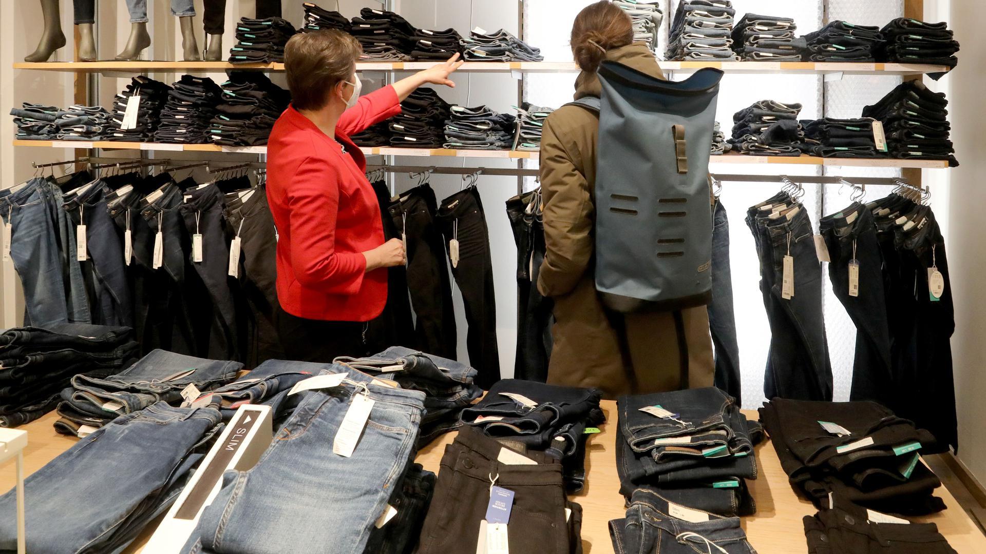 Zwei Frauen stehen in einem Geschäft vor einem Regal mit Hosen.