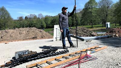 Ein Mann hält im Wörthböschelpark ein GPS-Messgerät in der Hand.