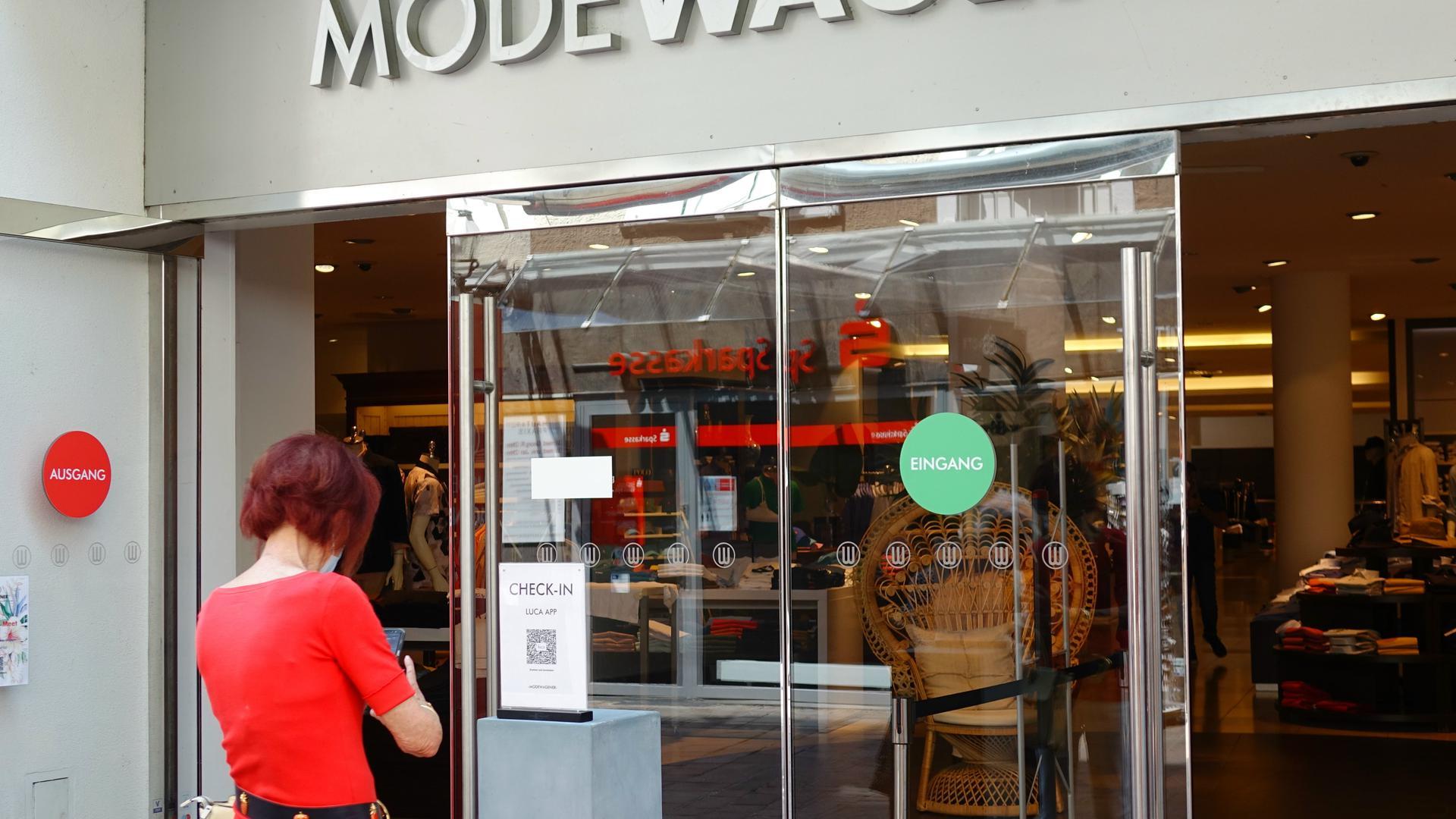 Frau vorm Modehaus scannt QR-Code