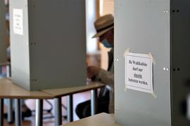 Ein Wähler mit Mund-Nasen-Schutzmaske sitzt in einer Wahlkabine.