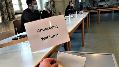 Wahlhelfer sitzen an einem Tisch im Wahllokal Werkrealschule Baden-Baden-Lichtental.