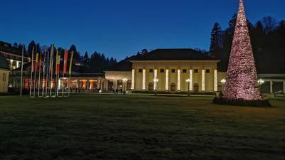 Das Kurhaus Baden-Baden ist in der Weihnachtszeit illuminiert. Auf der Wiese davor steht ein leuchtender Weihnachtsbaum.