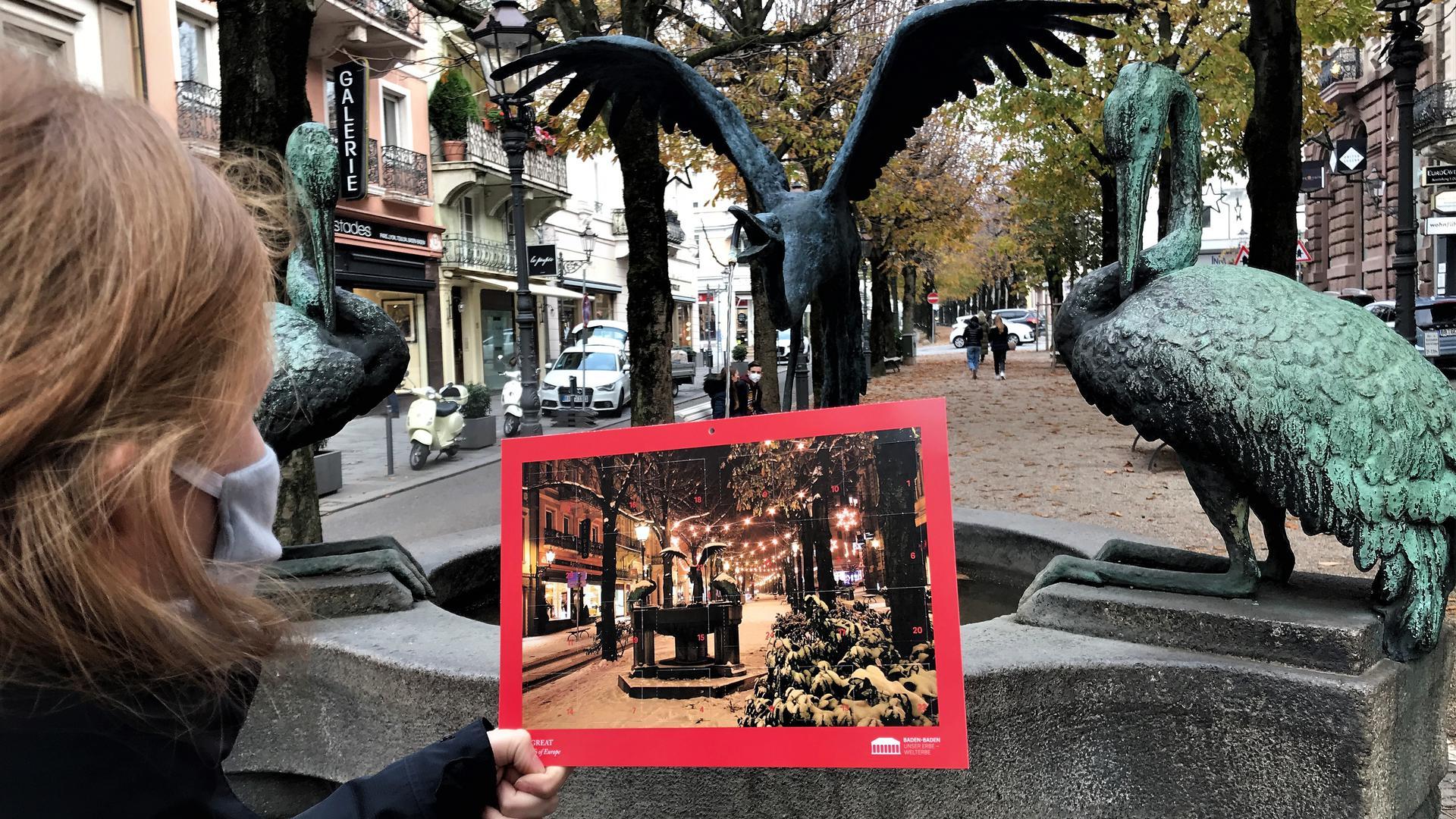 Ein Frau betrachtet den Welterbe-Adventskalender der Stadt Baden-Baden vor dem Reiherbrunnen in der Sophienstraße