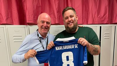 Gelungene Überraschung: Der Künstler freut sich über das von Ronny Zeller (links) besorgte Trikot eines bekannten Karlsruher Fußballers.