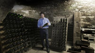 Flaschengärung: Winzer Robert Schätzle setzt auf das traditionelle Verfahren. Die Sektflaschen stecken in ein Brett mit Löchern, um sie hin und her drehen zu können.