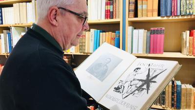 Christopher Pfleiderer blättert im Antiquariat im Baldreit in einem Exemplar. In den Regalen im Laden stehen rund 15.000 Bände.