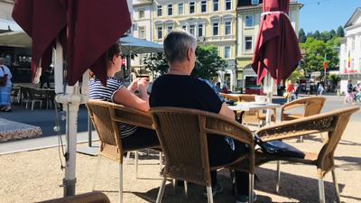Zwei Frauen sitzen im Außenbereich eines Restaurants in Baden-Baden.