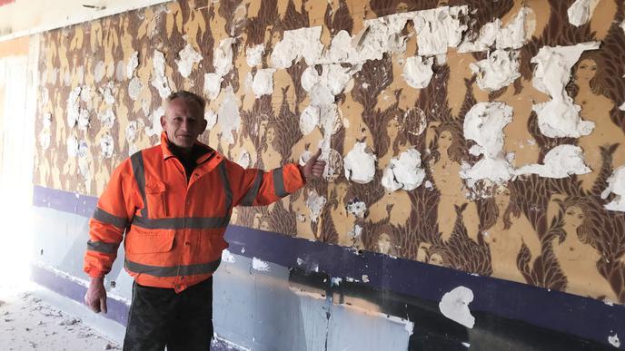 Eine alte Tapete mit Frauenkörpern hängt im Keller des Gebäudes, davor steht Siegfried Wilbur.