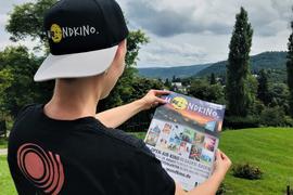 Nathalie Somville vom Studiokino Moviac studiert ein Mondkino-Plakat auf dem Areal für das Open-air-Kino im Rosenneuheitengarten in Baden-Baden. Der Nordschwarzwald dient als Kulisse.