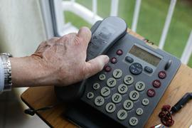 Eine Hand greift zum Hörer eines Telefons