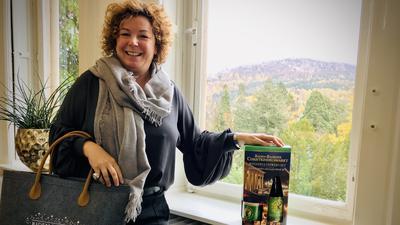 Die Baden-Badener Tourismuschefin Nora Waggershauser zeigt eine Einkaufstasche mit Christkindelsmarkt-Aufdruck und ein Paket mit Winzer-Glühwein und Tasse.