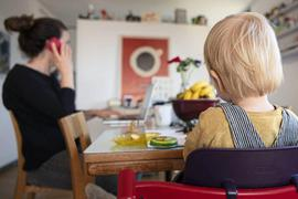 Ein Kind sitzt in der Küche am Esstisch während die Mutter arbeitet