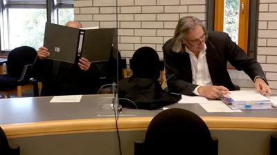 Ein Angeklagter in einem Prozess um eine Gruppenvergewaltigung hält sich vor Prozessbeginn im Gerichtsaal einen Aktenordner vor sein Gesicht. Rechts sitzt sein Anwalt Andreas Kniep. Vor mehr als 30 Jahren soll sich der Angeklagte als Leiter einer Pfadfindergruppe der Gruppenvergewaltigung schuldig gemacht haben.