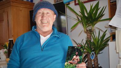 """Josef """"Tschamballah"""" Engler mit einem Foto, das ihn in jüngeren Jahren bei einer Asienreise zeigt."""