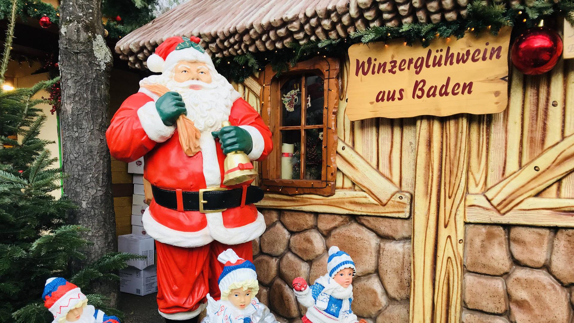 Eine Weihnachtsmann-Figur steht zur Dekoration neben einem Glühweinstand auf dem Christkindelsmarkt Baden-Baden.