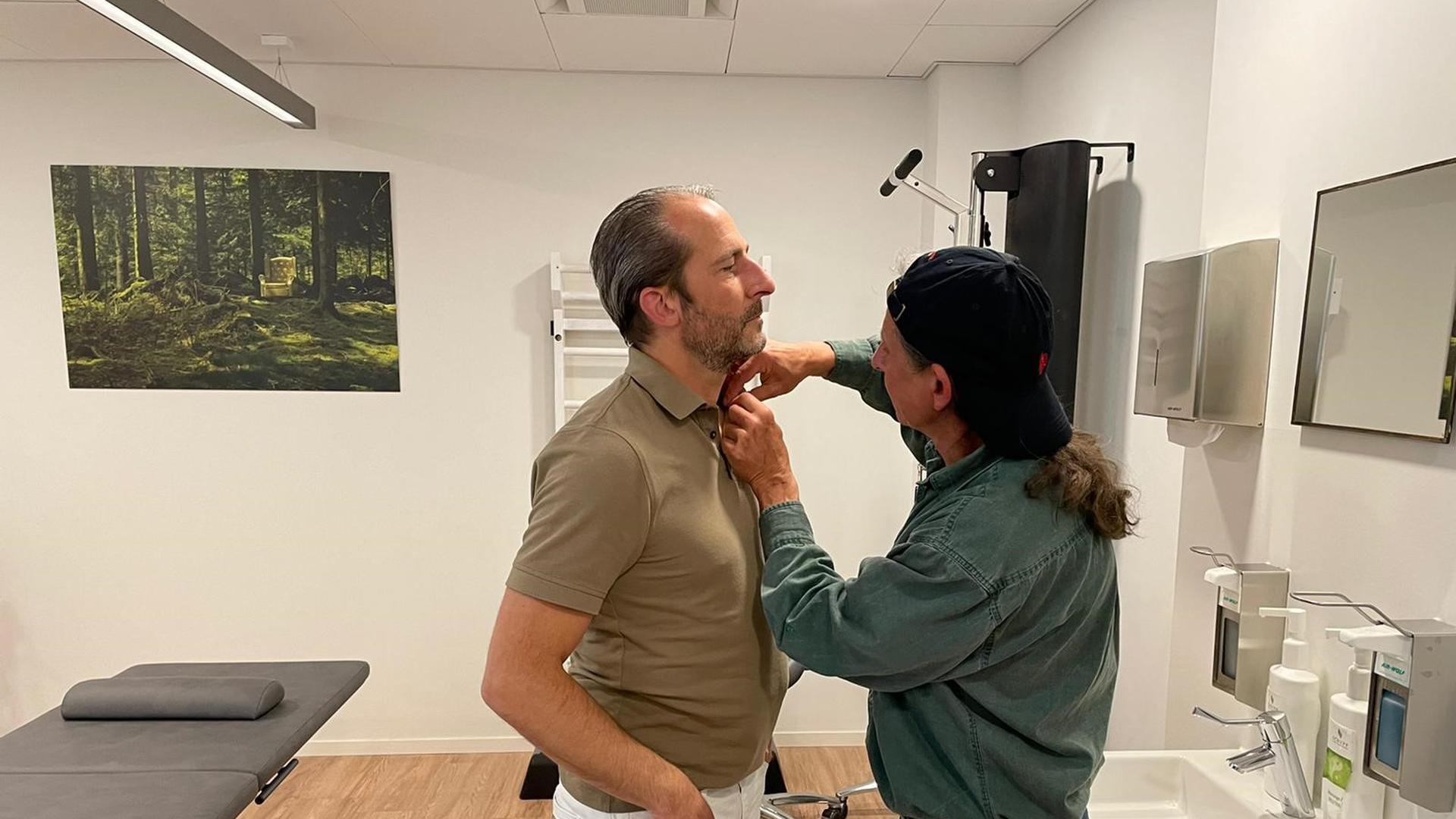 Physiotherapeut Mark Hohmann (links) wird für den Dreh des Fernsehteams des SWR mit einem Mikro ausgestattet.