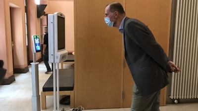 Benedikt Stampa, Intendant des Festspielhauses Baden-Baden steht mit einer Maske vor einem Gerät das Fieber misst.