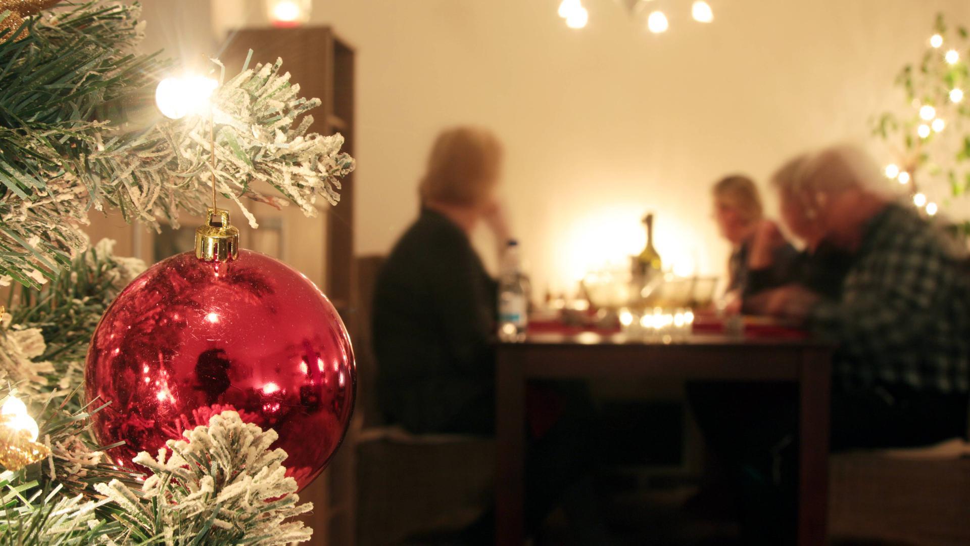 Familie sitzt an Heiligabend gemeinsam am Tisch und geniesst das Weihnachtsessen, model released  Family sits to Christmas Eve together at Table and enjoys the Christmas dinner Model released