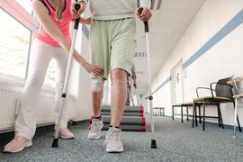 Ein Patienten lernt in der Reha mit Krücken zu laufen.