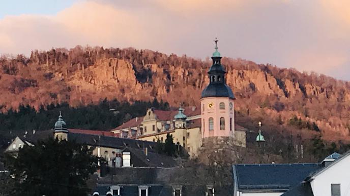 Überragt Baden-Baden: die Stiftskirche. Dahinter im Abendlicht die Battert-Felsen.
