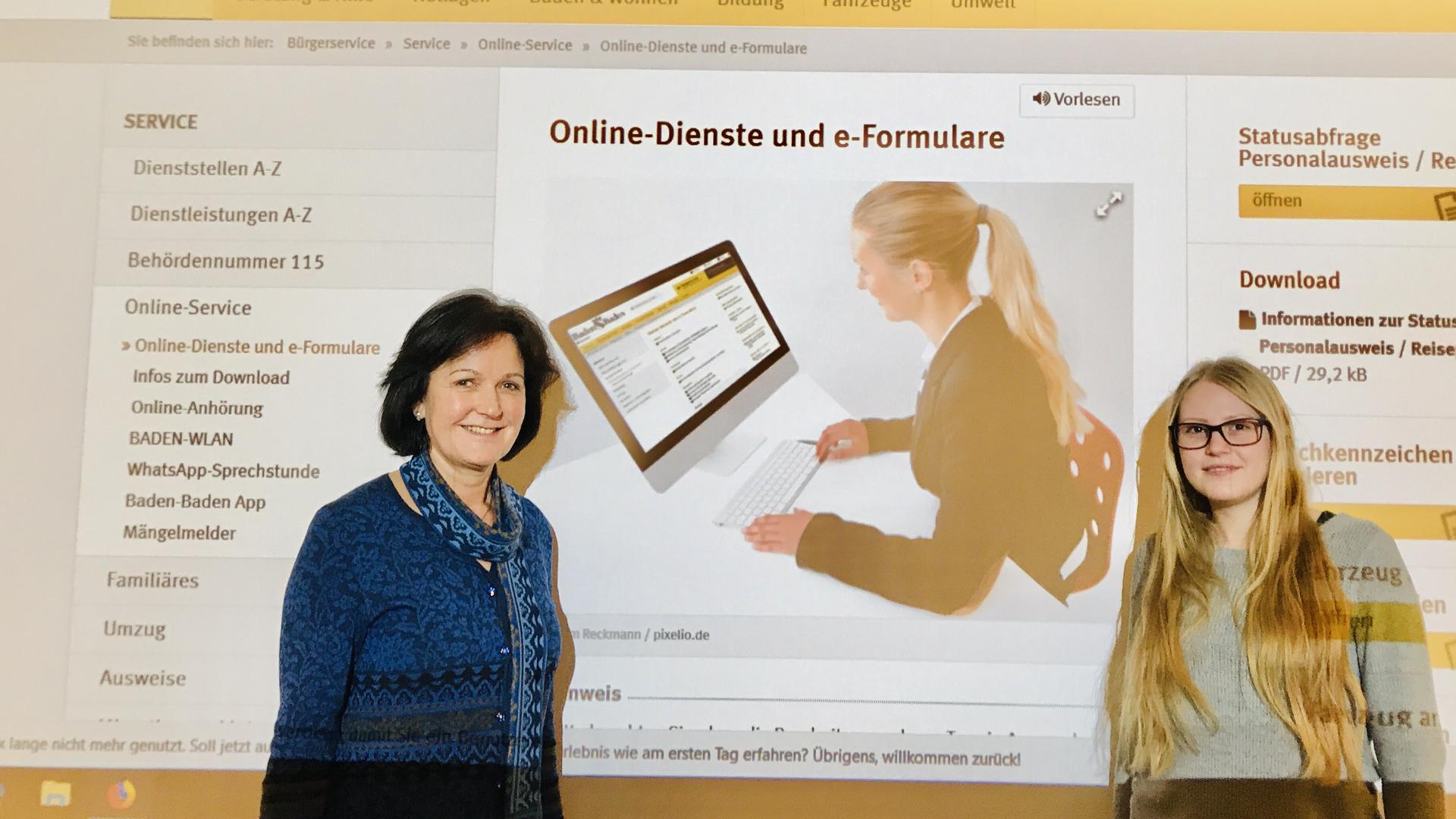 Oberbürgermeisterin Margret Mergen (links) und die Internetredakteurin der Stadt Baden-Baden, Hanna Matwich, stehen vor einer an eine Wand projizierte Ansicht der Homepage der Bäderstadt mit Online-Diensten und e-Formularen.