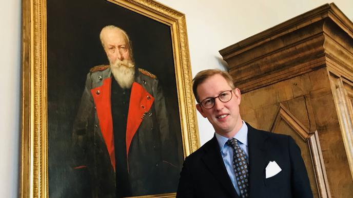 Bernhard Prinz von Baden steht in Schloss Salem vor einem Bild von Prinz Wilhelm von Baden.