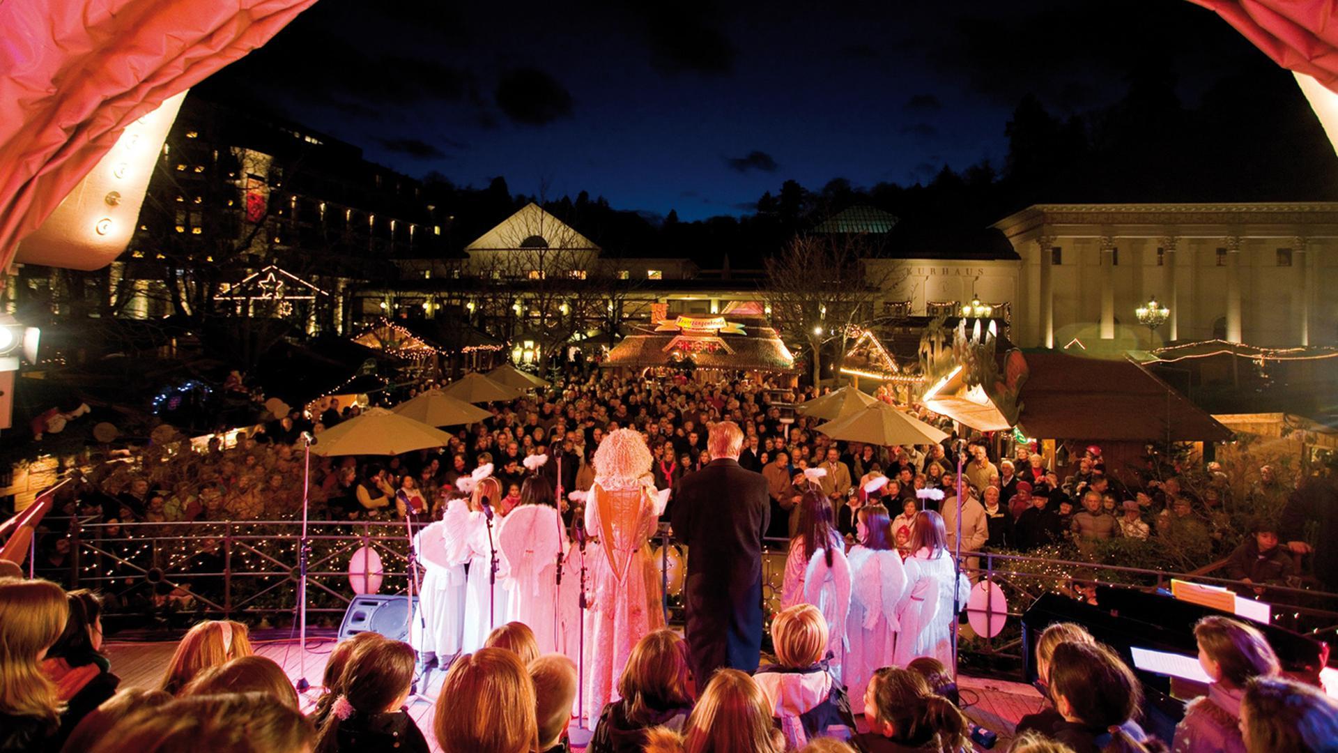 Ein Chor steht auf der Konzertmuschel vor dem Kurhaus in Baden-Baden, davor stehen beim Christkindelsmarkt zahlreiche Zuschauer.