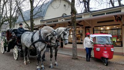 Eine Pferdekutsche und ein Tuk-Tuk stehen vor der Touristen-Information Baden-Baden.