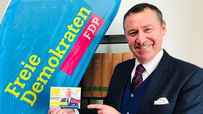 Der FDP-Bewerber für die Landtagswahl im Wahlkreis Baden-Baden, René Lohs, steht vor einem Banner seiner Partei und hält einen Wahlkampfflyer mit seinem Konterfei in der Hand.