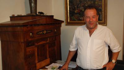 Mann vor antikem Schreibtisch