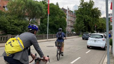 Zwei Radfahrer überholen einen Falschparker.