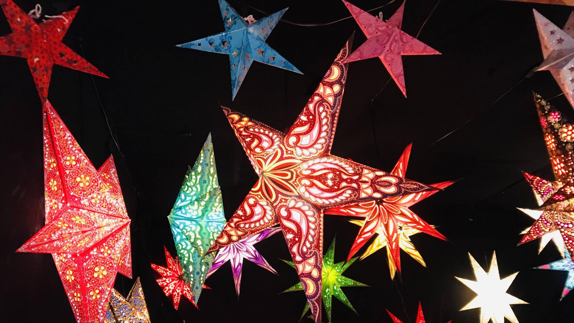 Leuchtende Weihnachtssterne hängen an einem Stand auf dem Weihnachtsmarkt in Baden-Baden.