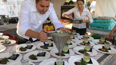 """Ronny Loll und seine Frau richten bei einer Veranstaltung von """"tafelvine""""  in der mobilen Küche eine Vorspeise an."""