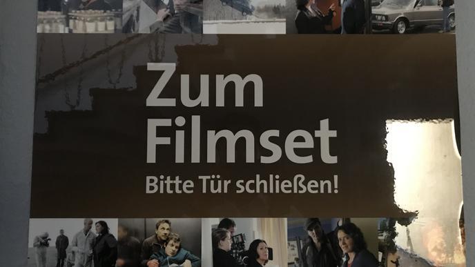 """Schild mit Titel """"Zum Filmset. Bitte Tür schließen!"""""""