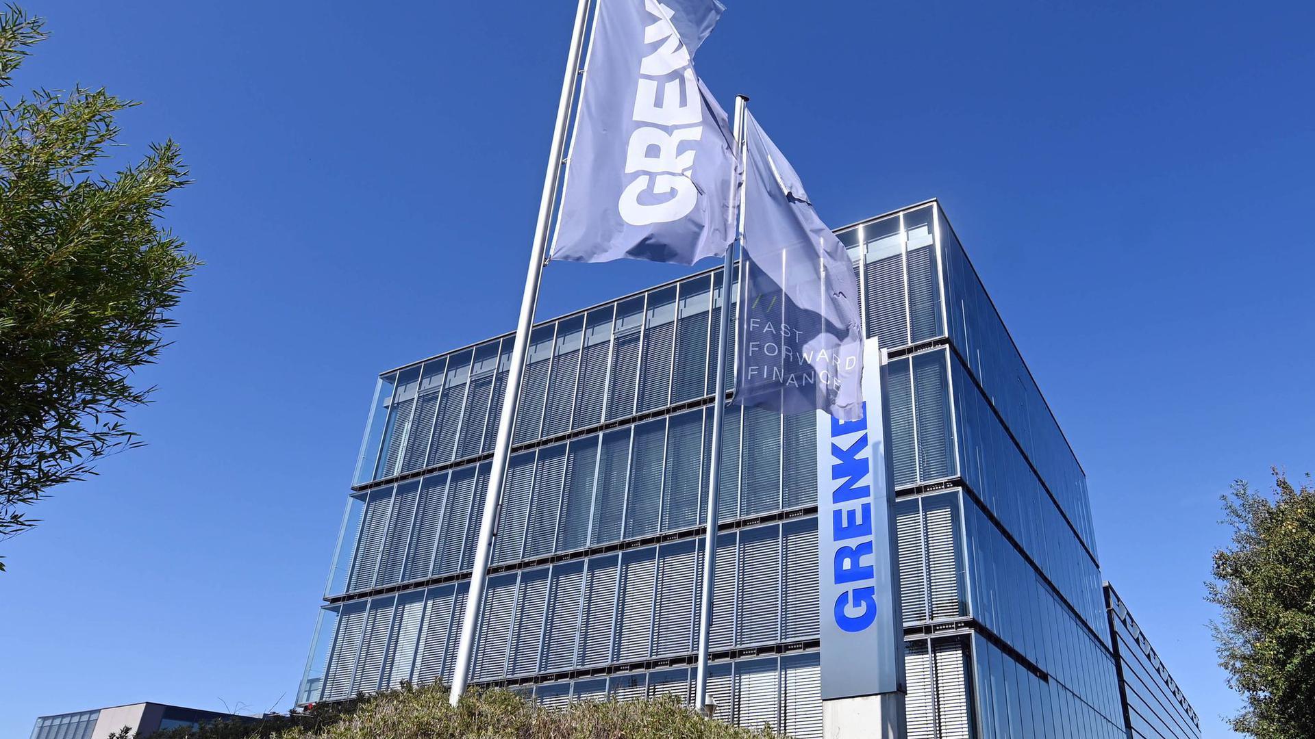 Flaggen mit dem Schriftzug des Finanzdienstleisters Grenke AG wehen an der Firmenzentrale.