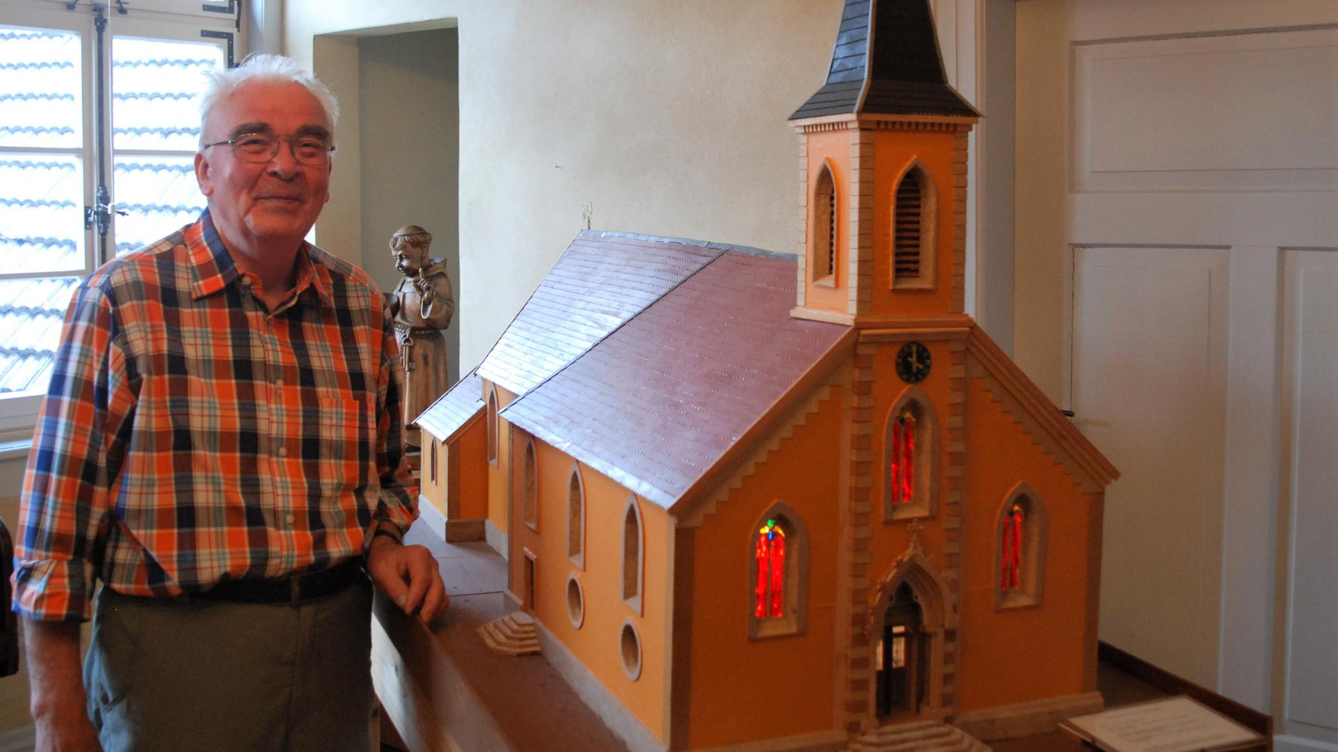 alter Mann neben Modellkirche
