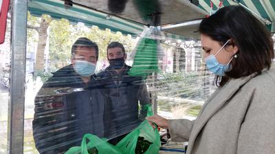 Eine Frau kauft auf dem Wochenmakt in Baden-Baden Blumen. Sie trägt eine Maske.