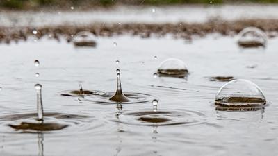 Regentropfen fallen in eine Pfütze und erzeugen durch den Aufprall kunstvolle Gebilde. +++ dpa-Bildfunk +++