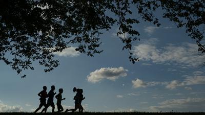 Menschen joggen, während die Sonne an einem klaren Frühlingstag untergeht.