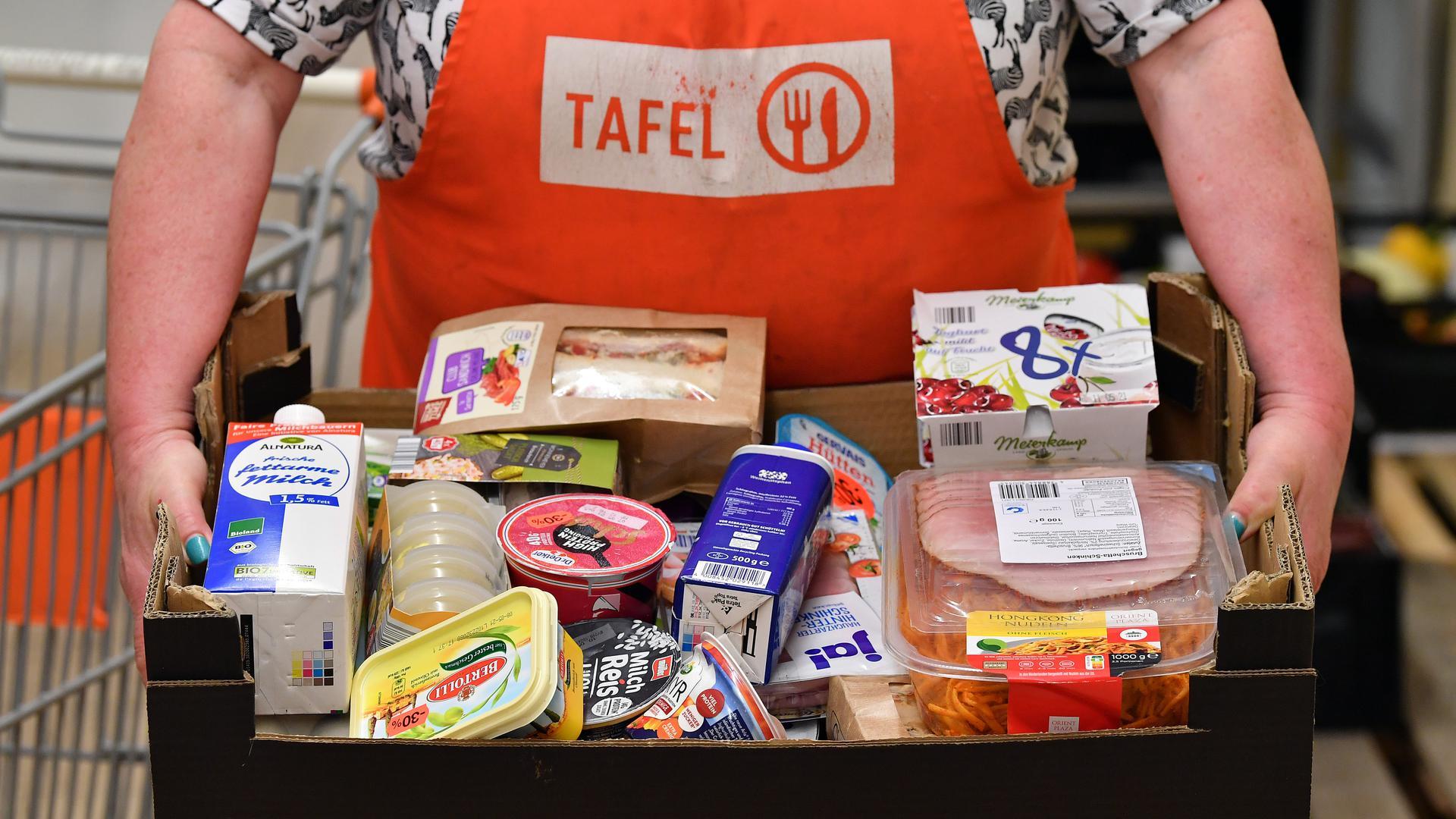 Eine Helferin der Tafel präsentiert die Kiste mit Lebensmitteln für einen Kunden.