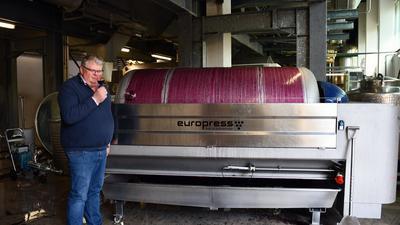 Mann an Weinpresse