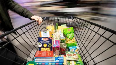 Ein Einkaufswagen wird durch einen Supermarkt geschoben. Die immer billiger werdenden Preise für Lebensmittel stehen in der Kritik.