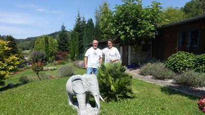 Ein Ehepaar steht nebeneinander in einem Garten an einem Stein-Elefanten.