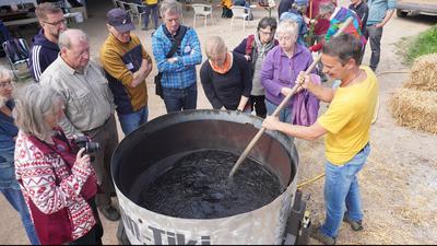 Gruppe um einen großen Topf mit schwarzer Flüssigkeit