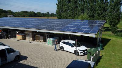 An die Zapfstelle: Ein Mitarbeiter der Firma Veith schließt einen Firmenwagen an die Ladesäule an, die von den Solarzellen auf dem Dach gespeist werden.