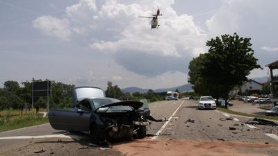 Straße mit kaputtem Auto und Trümmerteilen. Hubschrauber fliegt darüber.