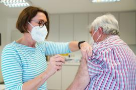 Eine Hausärztin verabreicht eine Impfung gegen Covid-19.
