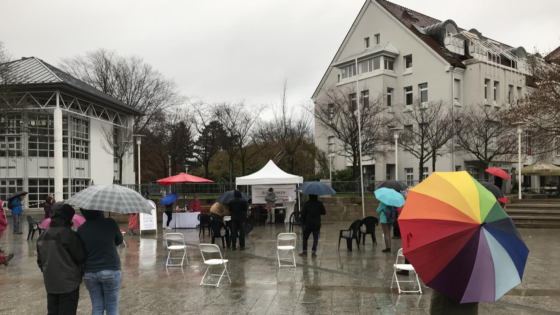 Menschen mit Regenschirmen auf dem Europa-Platz in Bühl