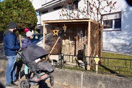 Ein Mann mit Kinderwagen betrachtet eine Krippe am Mooser Krippenweg.